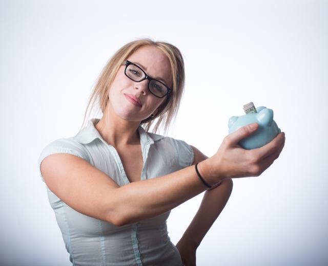 貯金箱を持って微笑む女性のイメージ画像
