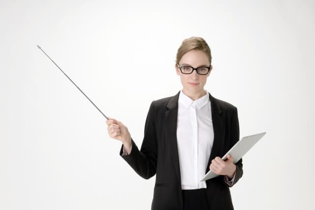 指示棒を持つスーツ姿の女性のイメージ画像